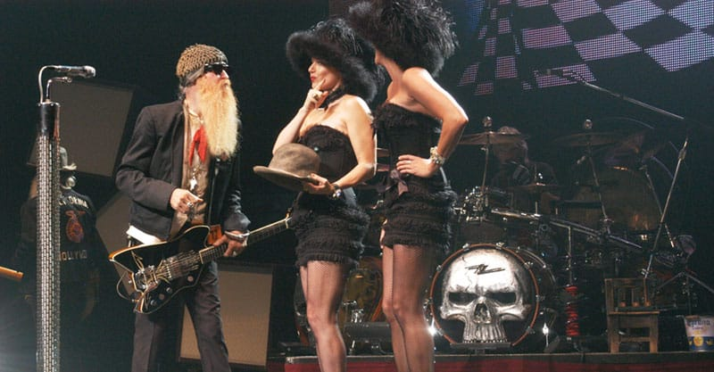 Half of ZZ Top on stage with two women